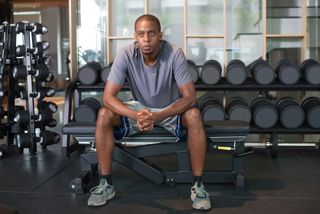 Pensive black man relaxing in gym and looking away