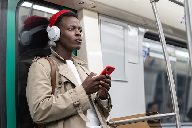 Pensive black man in subway train thinking using cellphone listens to music with wireless headphones