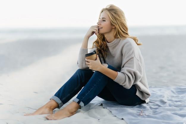 모래에 앉아서 바다를보고 청바지에 잠겨있는 blinde 여자. 해변에서 커피를 마시는 편안한 백인 여자의 야외 초상화.