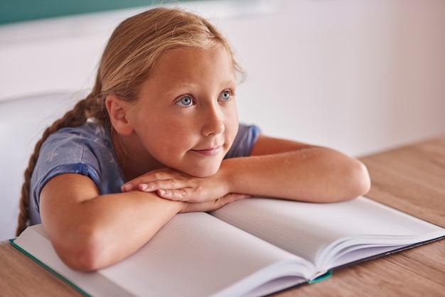 物思いにふけるブロンドの髪の女の子が目をそらしている 無料写真