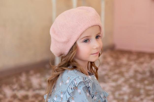 長い巻き毛の物思いにふける金髪の少女。秋の通りのベレー帽とドレスのかわいい笑顔の女の子のクローズアップの肖像画。子供の頃の概念。