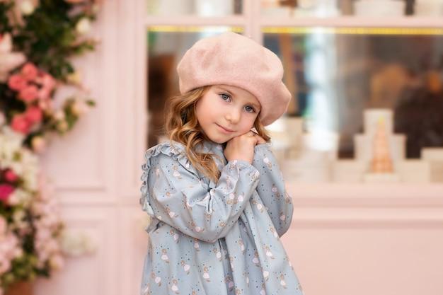 長い巻き毛の物思いにふける金髪の少女。秋の通りのベレー帽とドレスのかわいい笑顔の女の子のクローズアップの肖像画。