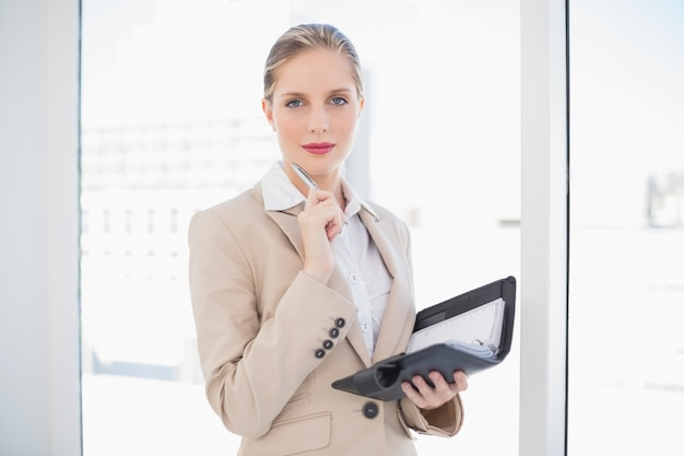 Pensive blonde businesswoman holding datebook
