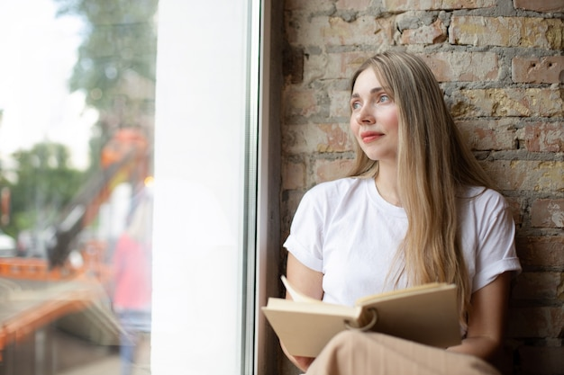 白いtシャツを着た物思いにふける金髪の白人女性は、レンガの壁に寄りかかって本を読んで大きな窓の外を見る