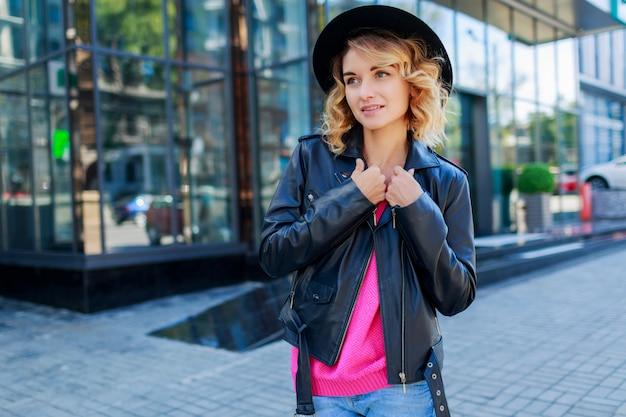 Pensive  blonde short haired woman walking on streets of big modern city. fashionable urban outfit. unusual pink sunglasses.