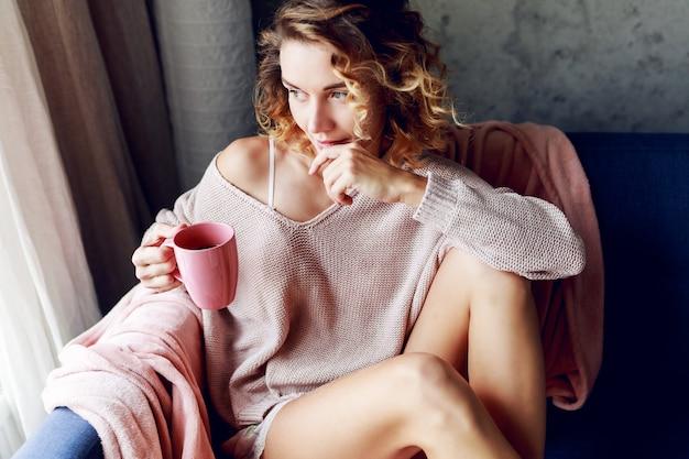 ピンクのニットの居心地の良いラウンジで物思いにふけるブロンドの女性は、お茶を飲みます。朝早く。ホーム。