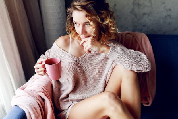 Pensive blonde woman in pink knitted cozy lounge wear drinking tea . early morning.  home .