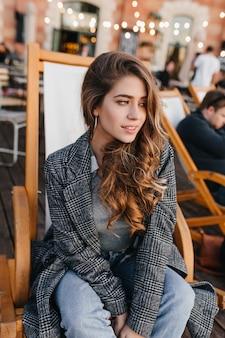 Задумчивая голубоглазая девушка с бледной кожей сидит в кресле в летнем кафе и смотрит в сторону