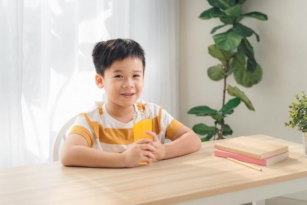 テーブルでジュースを飲み、家で孤立して目をそらしている物思いにふける少年