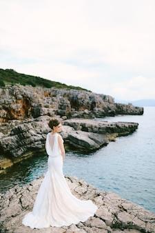 Задумчивая невеста в длинном кружевном белом платье стоит на каменном берегу над морем