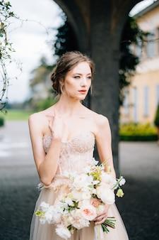 ピンクのドレスを着た物思いにふける花嫁は彼女の手に花束を持っています