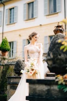 花の花束とピンクのドレスを着た物思いにふける花嫁は、彼女の頭を頭を下げて立っています。