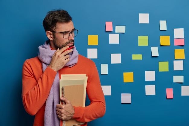 Studente maschio pensieroso brunet tiene il mento, ha setole spesse, tiene i taccuini necessari, indossa sciarpa e maglione
