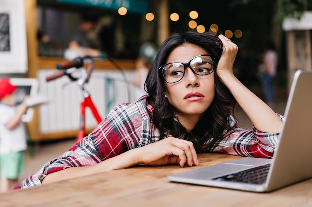 잠겨있는 갈색 머리 프리랜서 야외 앉아 멀리 찾고. 컴퓨터를 사용하는 안경에 피곤 된 여성 국제 학생의 초상화.