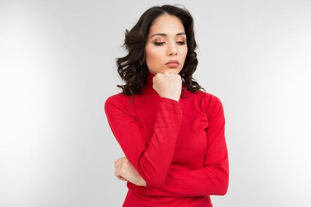 Задумчивая брюнетка в красной водолазке на фоне белой студии.