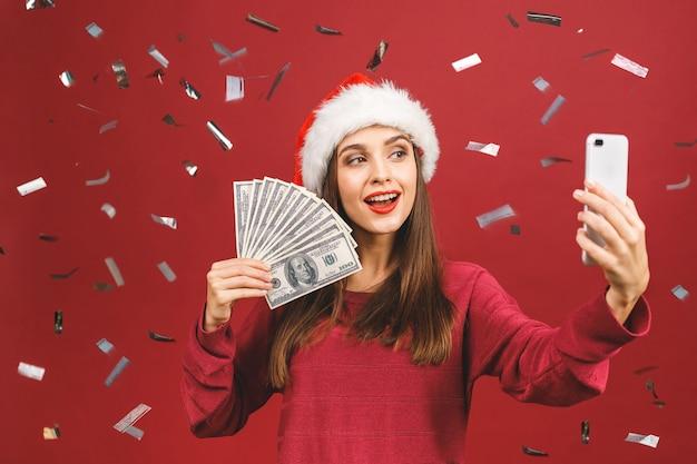 お金を押しながらselfieを作るクリスマス帽子の物思いにふけるブルネットの女性