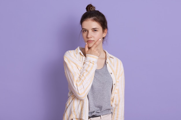 Pensive brunette young woman with bun, lady wearing casual clothing, keeping hand on her chin