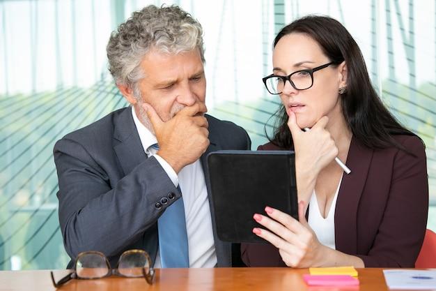物思いにふけるビジネス部門の同僚がタブレットを一緒に使用し、プレゼンテーションを見たり、画面を見たりします。
