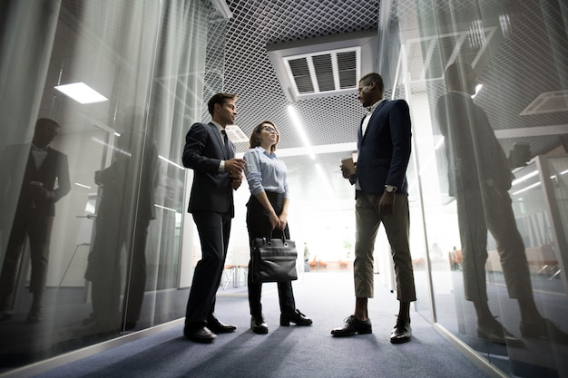 Pensive business employees drinking coffee in office corridor
