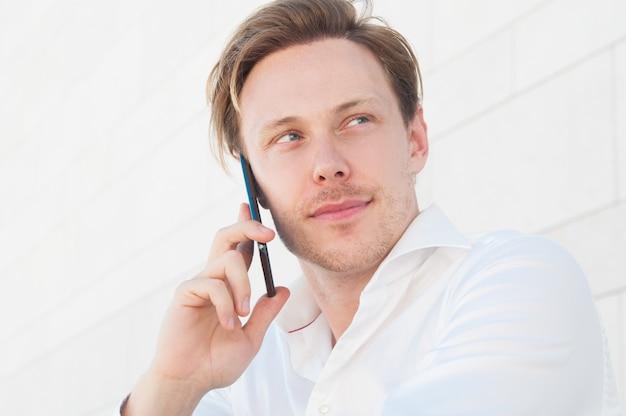 屋外でスマートフォンを呼び出す物思いにふけるビジネスマン