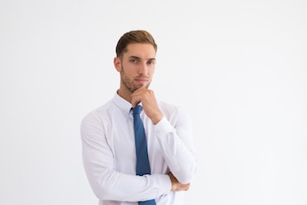 Pensive business man touching chin and looking at camera