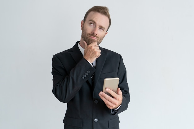 Pensive business man touching chin, thinking and holding smartphone.