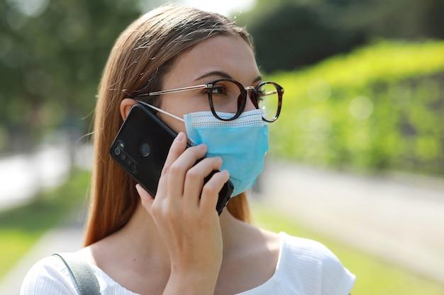 街でコロナウイルスを回避するサージカルマスクを使用してスマートフォンで話している物思いにふけるビジネス女性