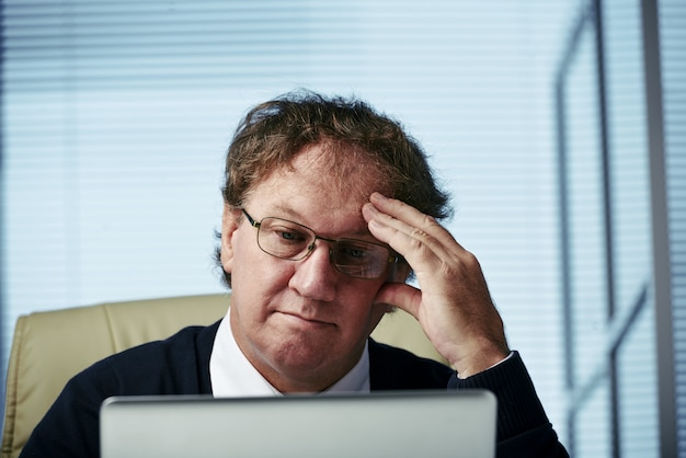 Pensive businessman analyzing further strategic moves represented on digital tab