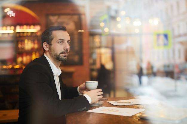 Задумчивый бизнесмен, наслаждаясь кофе в роскошном ресторане