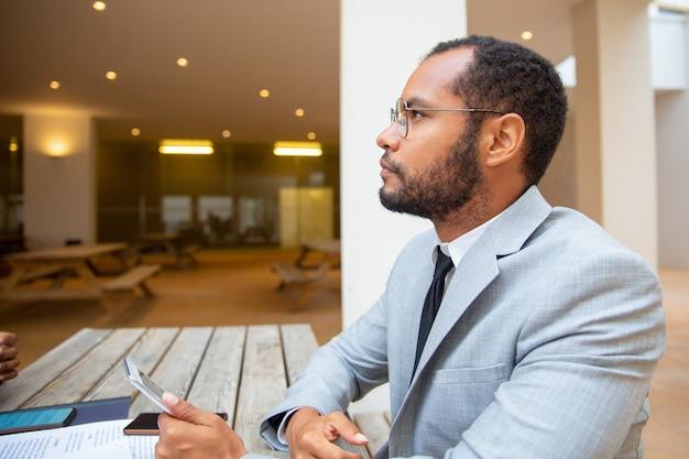 Pensive businessman holding digital gadget