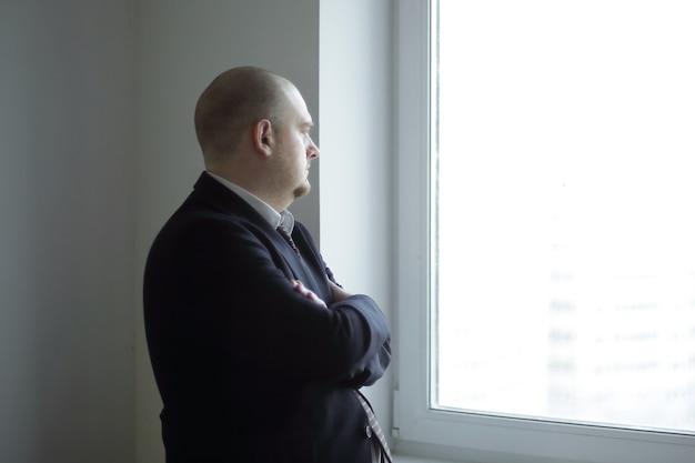 空白のオフィスの窓を見ている物思いにふけるビジネスマン