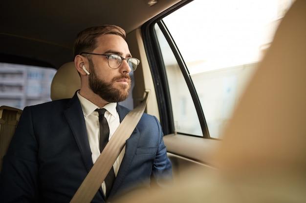 택시에 앉아 생각에 잠겨있는 사업가