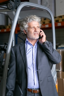 Pensive businessman standing in warehouse near forklift and talking on cellphone