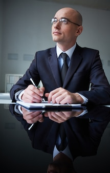 Pensive businessman with clipboard