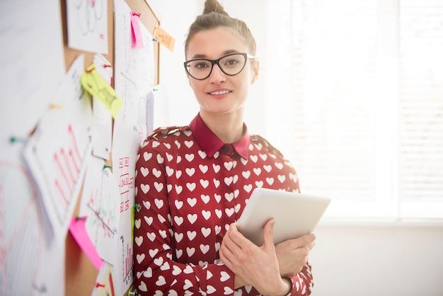 彼女のデジタルタブレットでポーズをとる物思いにふける実業家