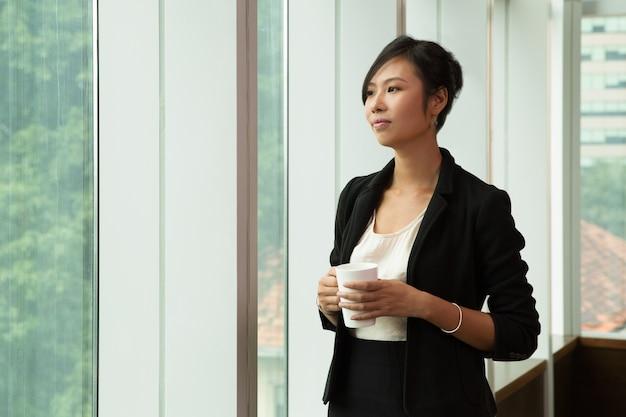 Donna d'affari pensive in piedi con la tazza di caffè