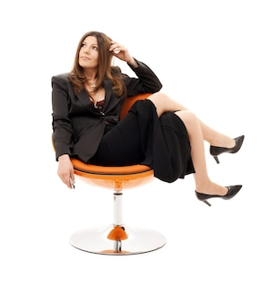 Pensive businesswoman with cell phone over white