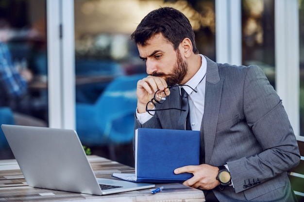 Pensive caucasian bearded businessman in suit holding eyeglasses and agenda while sitting in cafe terrace. on table is laptop.