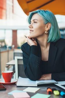 잠겨있는 백인 파란 머리 아가씨 커피 숍에 앉아 몇 가지 메모를하는 동안 멀리보고