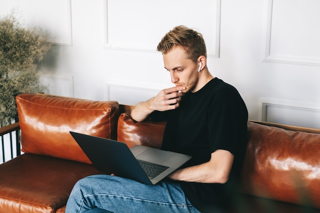Pensive caucasian man mobile developer programmer writes program code on a laptop computer in home office.