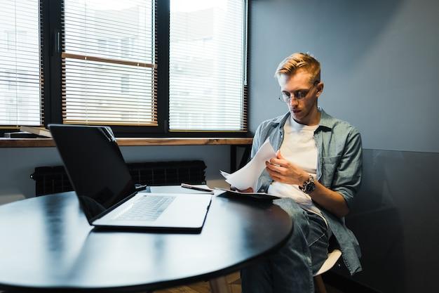 Задумчивый кавказский человек, работающий с ноутбуком в домашнем офисе и смотрящий на бумажные документы, рассчитывающий счета