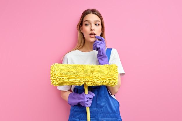 床をきれいに洗うために手にモップを持っている物思いにふける白人女性