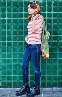 Задумчивая кавказская молодая девушка с сеткой с овощами на зеленой стене на улице