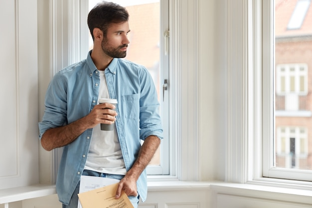 Pensive chairman with dark bristle, dressed in stylish shirt, holds takeaway coffee, papers, studies taxes