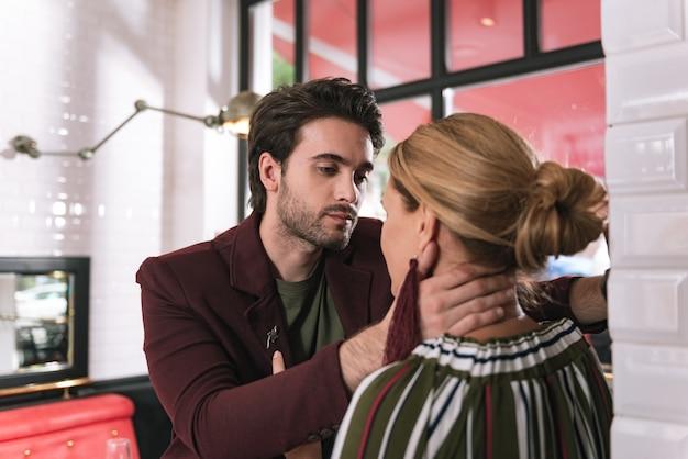 Задумчивый очаровательный мужчина трогает женщину и позирует на размытом фоне
