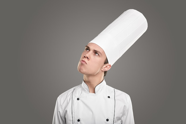 Pensive chef in white uniform looking up