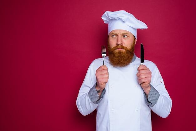 수염과 빨간 앞치마가있는 잠겨있는 요리사가 칼을 손에 쥐고 있습니다.