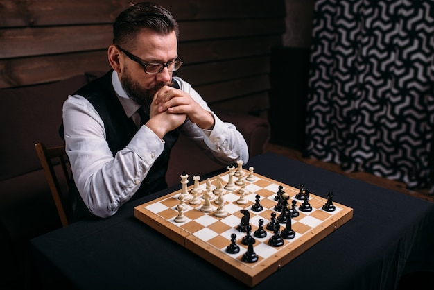Pensive chess player thinking about game strategy