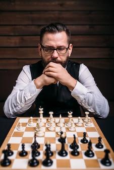 Задумчивый шахматист думает о стратегии игры
