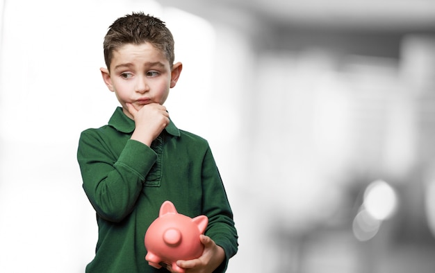 Pensive child with pig piggy bank